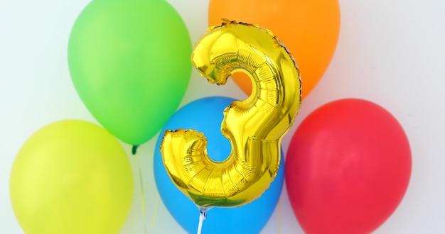 Gouden folie nummer 3 vieringsballon op een kleur