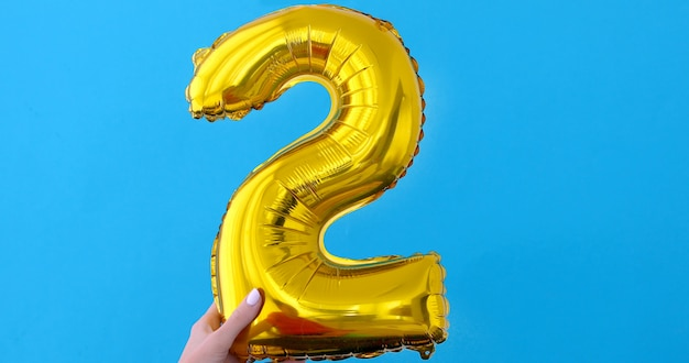 Gouden folie nummer 5 vieringsballon op een blauw