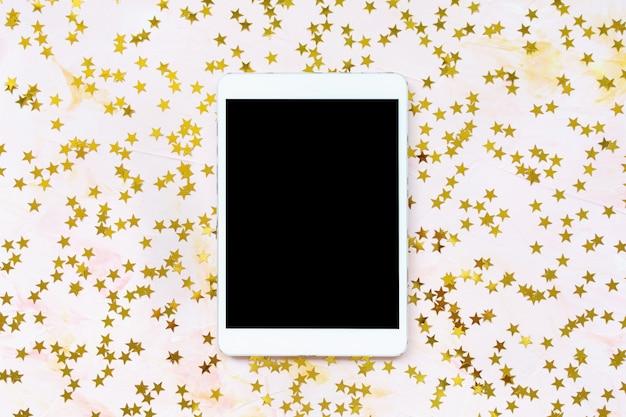Gouden folie sterren confetti decoratie en tablet op roze achtergrond. kerstviering, winter en dromen concept. bovenaanzicht, plat lag, bespotten