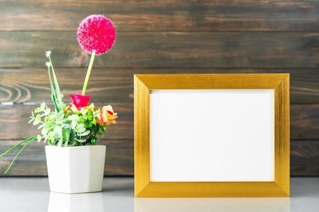 Gouden frame en het kunstmatige boeket van de bloemenvaas over lijst met houten muurachtergrond