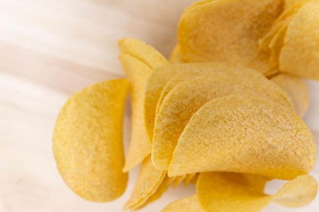 Gouden gegolfde aardappelen. hoop chips op een witte achtergrond. geen gezond dieet. fastfood gebakken