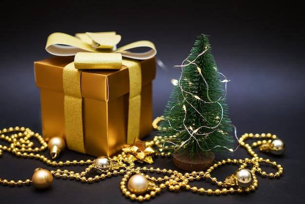 Gouden geschenk bij een kleine kerstboom met ballen en kralen op een zwarte achtergrond