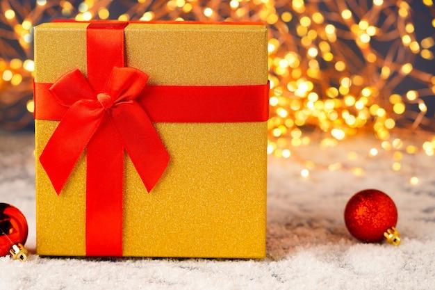 Gouden geschenkdoos met een rood lint close-up op een bokeh background