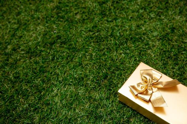 Gouden geschenkdoos met een strik op groen gras in een tuin