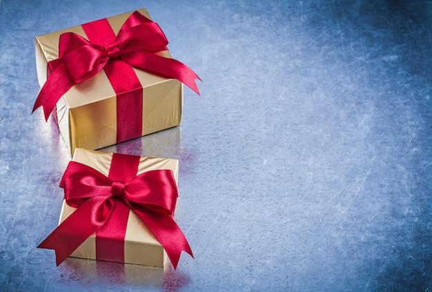 Gouden geschenken verpakt met rode bogen op bekrast metalen achtergrond