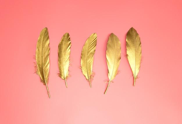 Gouden glanzende veren op een rij op pastel roze achtergrond, plat leggen, retro, modern, kleurrijk stijlvol concept bovenaanzicht.