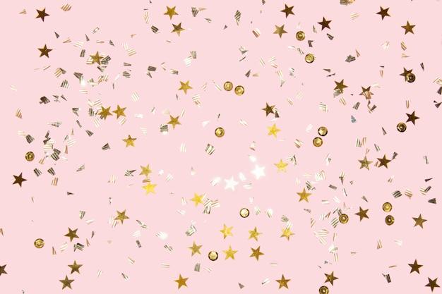 Gouden glanzende vliegende confetti op een roze feestelijke achtergrond als achtergrond voor elk kerstproject