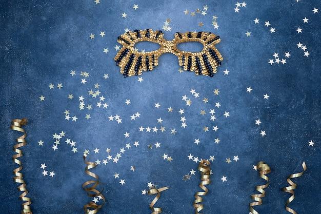 Gouden glinsterende masker en serpentijn met gouden sterren op blauw.