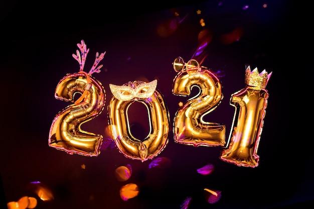Gouden glinsterende nummers 2021 op zwarte achtergrond in carnavalaccessoires, nieuwjaarsfeestconcept. confetti vliegt.
