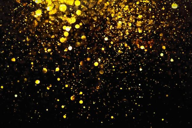 Gouden glitter bokeh verlichting textuur wazig abstracte achtergrond voor verjaardag, jubileum, bruiloft, oudejaarsavond of kerstmis