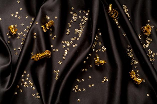 Gouden glitter en linten op zwarte achtergrond