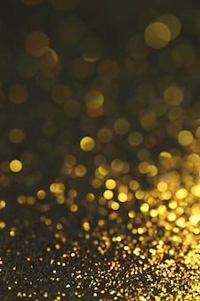 Gouden glitter macro met glanzende bokeh op een zwarte achtergrond. lichtend textuur.