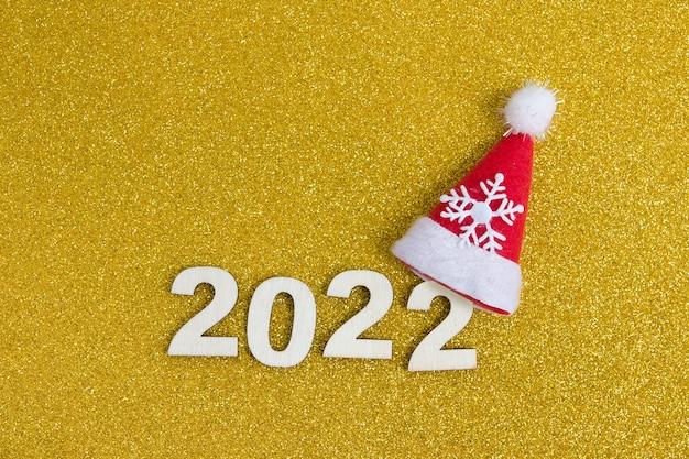 Gouden glitter textuur achtergrond sprankelend glanzend inpakpapier en nieuwjaarsnummers in kerstmuts