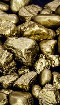 Gouden goudklompjes geïsoleerd op een zwarte ondergrond. luxe concept en goud.