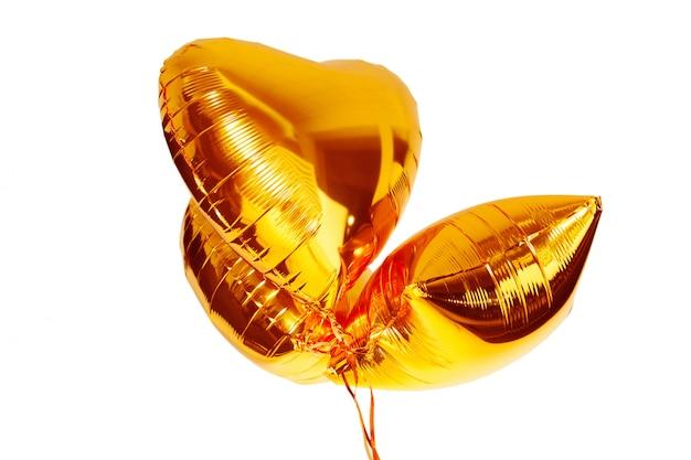 Gouden grote hart metaalballon die op wit wordt geïsoleerd