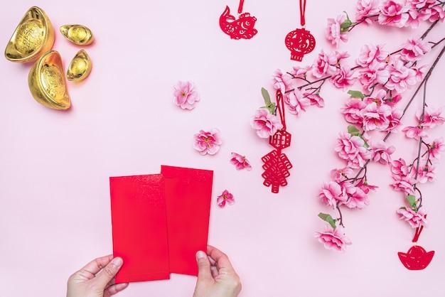 Gouden gyozas en bloemen op roze met handen met blanco kaarten