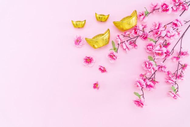 Gouden gyozas en bloemen op roze