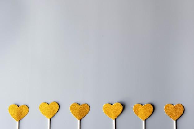 Gouden harten op grijze document muur. fijne valentijnsdag, minimalisme concept