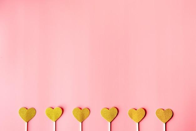 Gouden harten op roze document muur. gelukkige valentijnsdag, minimalisme concept gouden harten op grijze papieren muur. fijne valentijnsdag, minimalisme concept Premium Foto