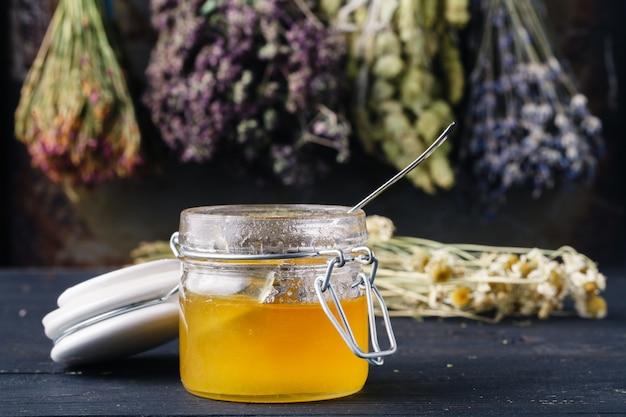 Gouden honing in glazen pot op rustieke tafel