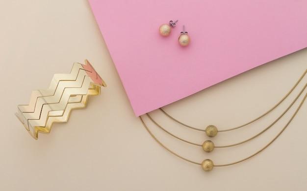 Gouden juwelen die op roze en beige achtergrond worden geplaatst