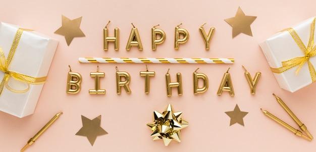 Gouden kaarsen met gelukkige verjaardag en geschenken