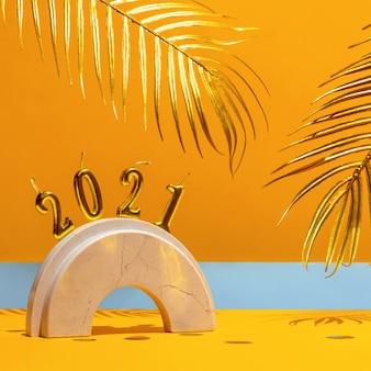 Gouden kaarsen met het nieuwe jaar 2021 op de marmeren boog, palmbladeren, confetti op een gele achtergrond met de horizon. feestelijk trendstilleven.