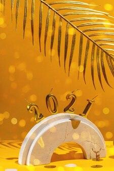 Gouden kaarsen met het nieuwe jaar op de marmeren boog, palmbladeren, kerstbomen, confetti