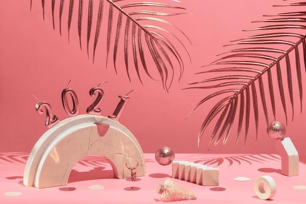 Gouden kaarsen met het nieuwe jaar op de marmeren boog, palmbladeren