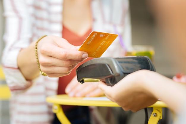 Gouden kaart. bezoeker van een café die een gouden kaart geeft terwijl een serveerster een terminal vasthoudt