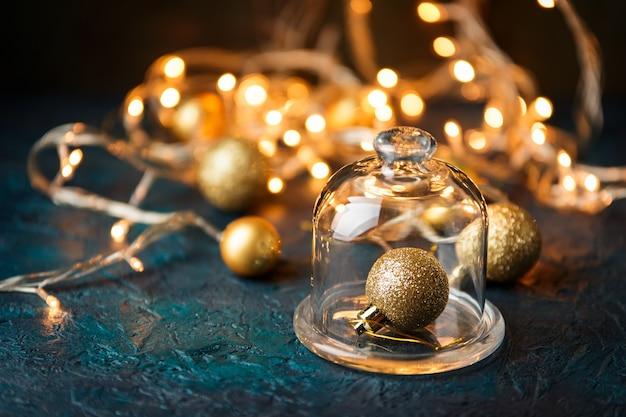 Gouden kerstbal onder de glazen dop over wazig licht.