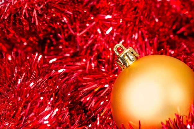 Gouden kerstbal op de onscherpe achtergrond van klatergoud