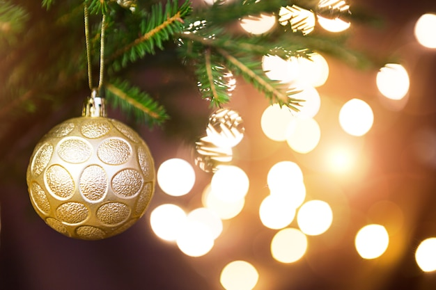Gouden kerstbal op een levende tak van een dennenboom met gouden lichten van slingers in defocus. nieuwjaar, kerstmis, vakantie achtergrond, bokeh, kopie ruimte