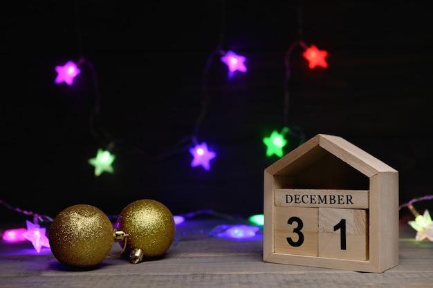 Gouden kerstballen, houten blokjes met de cijfers 31 december met een veelkleurige slinger