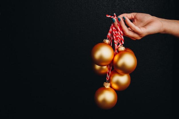 Gouden kerstballen in de hand van de vrouw geïsoleerd op zwarte achtergrond