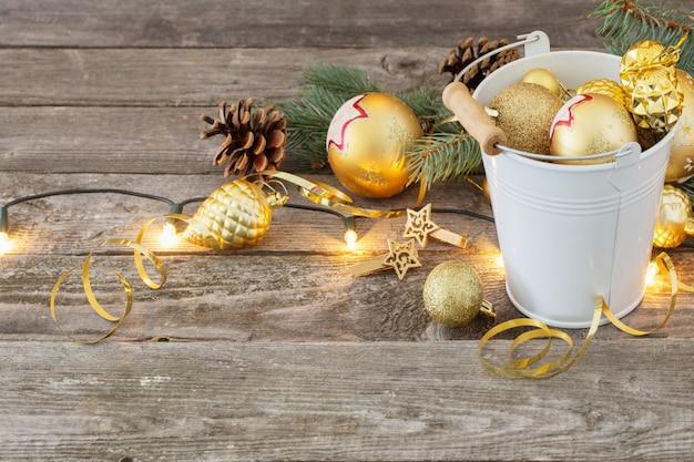 Gouden kerstballen in emmer op houten achtergrond