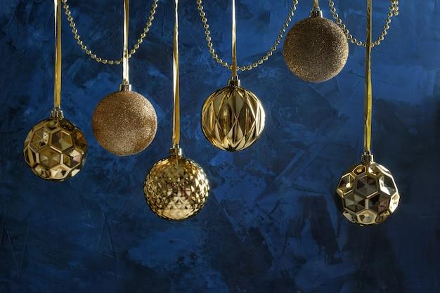 Gouden kerstballen opgehangen aan een lint, kralen.