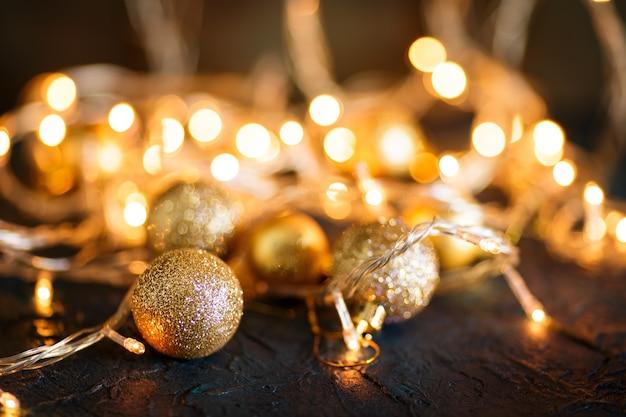 Gouden kerstballen tegen onscherpe lichten.