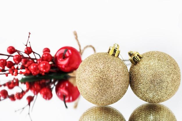 Gouden kerstballen worden weerspiegeld in het spiegeloppervlak