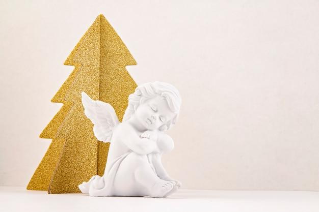 Gouden kerstboom en witte engel.