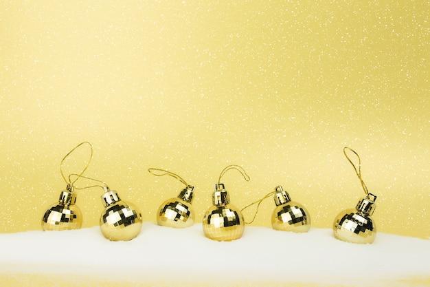 Gouden kerstboomballen op goud met nepsneeuw.