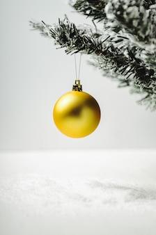 Gouden kerstboomstuk speelgoed bal op kunstmatige spar met sneeuw op wit.