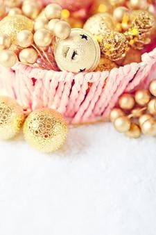 Gouden kerstmisspeelgoed op een lichte achtergrond.