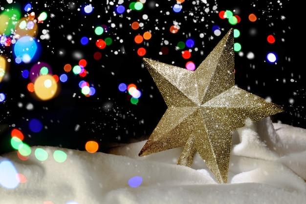 Gouden kerstster in de sneeuw. intreepupil lichten op de achtergrond. decoratie voor de kerstboom. kerst achtergrond