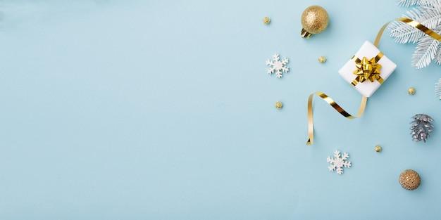 Gouden kerstversiering op pastel blauwe achtergrond