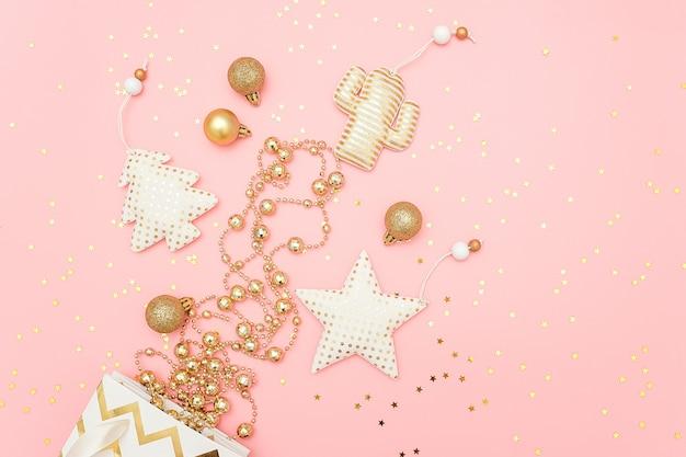 Gouden kerstversieringen vliegen uit zak en confetti sterren op roze prettige kerstdagen of gelukkig nieuwjaar concept.