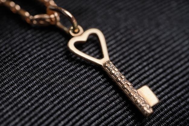 Gouden ketting met een hanger in de vorm van een sleutel op een zwarte doek.