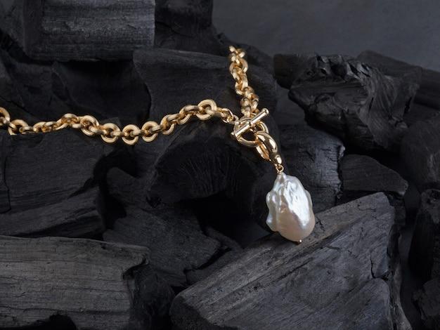 Gouden ketting met witte barokke parelhanger op zwarte kolenachtergrond