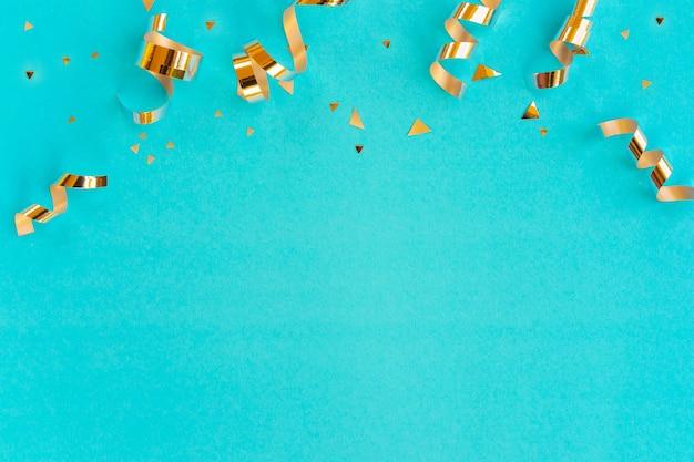 Gouden kleur van rollend lint en confetti op groenblauw achtergrond