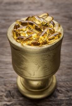 Gouden kom met gouden dieetpillen. vitamine e.